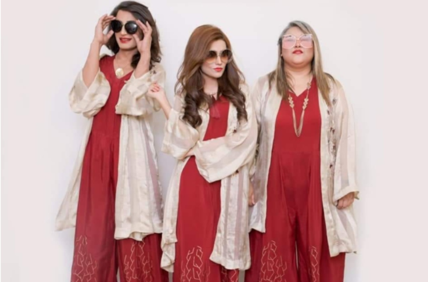 Three women stand wearing matching outfits that are a red traditional pakistan dress with a flowing cream cardigan wrap over the top. they are all wearing sunglasses standing against a white wall and looking playfully at the camers