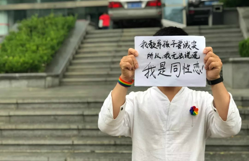 A gay kindergarten teacher in China holds a sign reading 'I am gay' as he files a case with the labor court (Photo: Weibo)