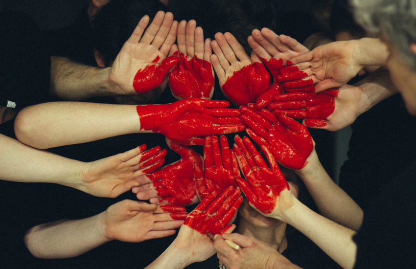 Hands making a heart of red paint