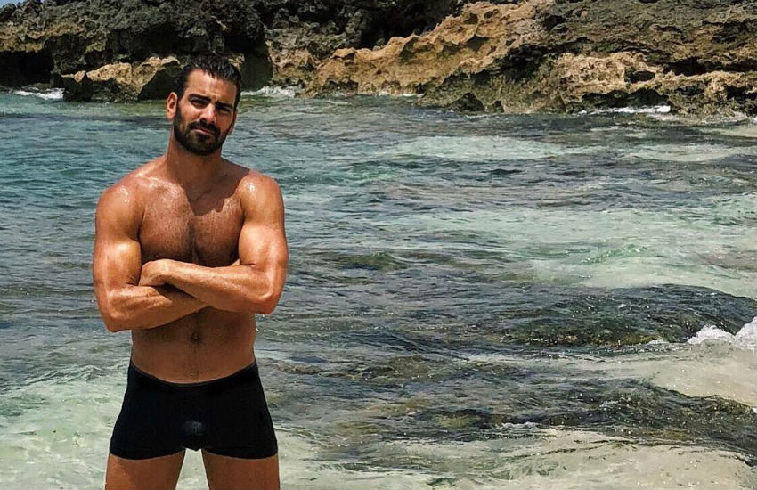Nyle DiMarco in his underwear on a beach