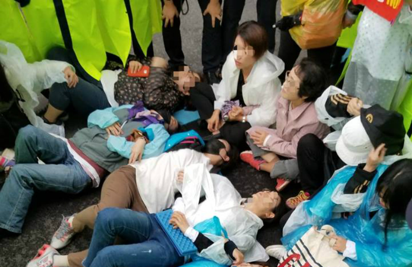 Protesters lie down on the street to prevent an LGBTI pride parade in Jeju, South Korea. Faces are blurred to comply with South Korean law. (Photo: Michelle Jones)
