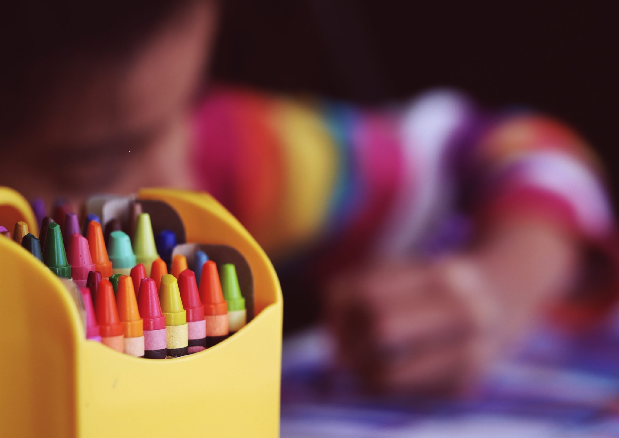 A child uses crayons to draw a picture