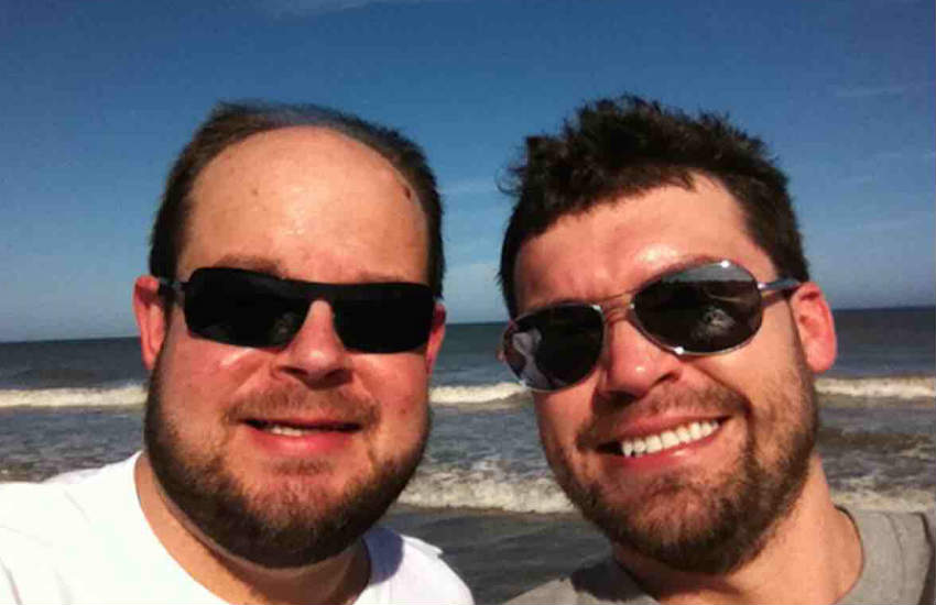 Two men in sunglasses, smiling, posing for a selfie.