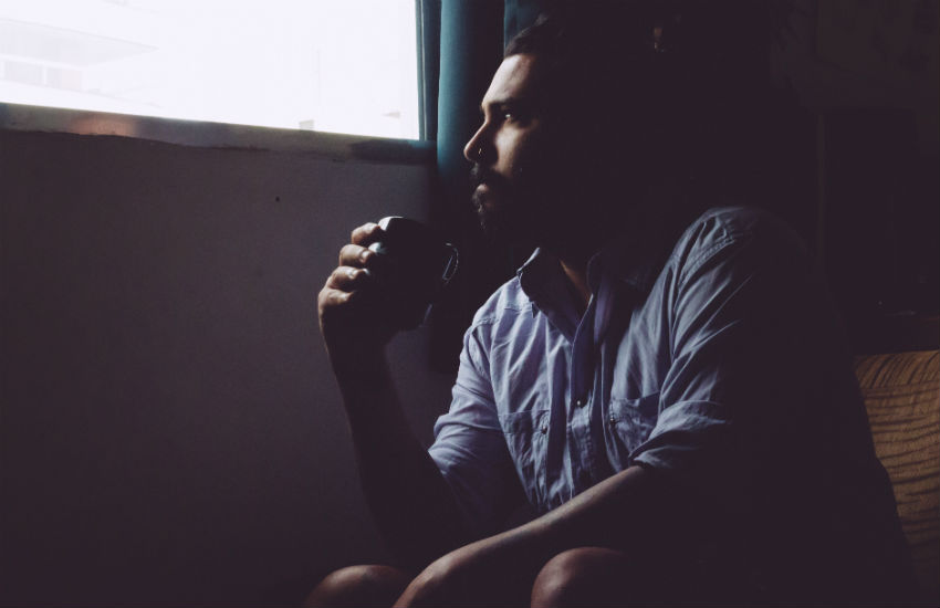 A man in rehab looks out of a window