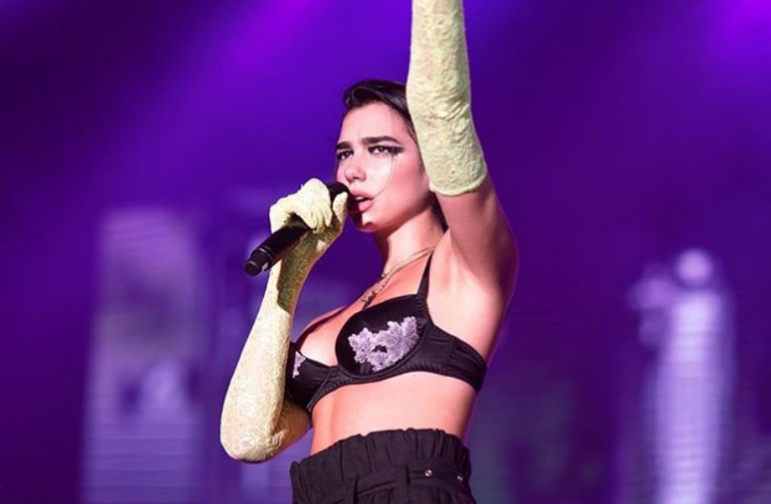 dua lipa on stage holding one arm up and singing into a microphone