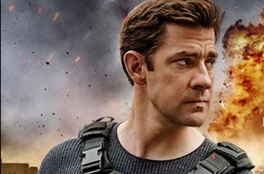 a promotional shot of jack ryan. john krasinski stands looking over his shoulder with a determined look on his face there is an explosion happening behind him