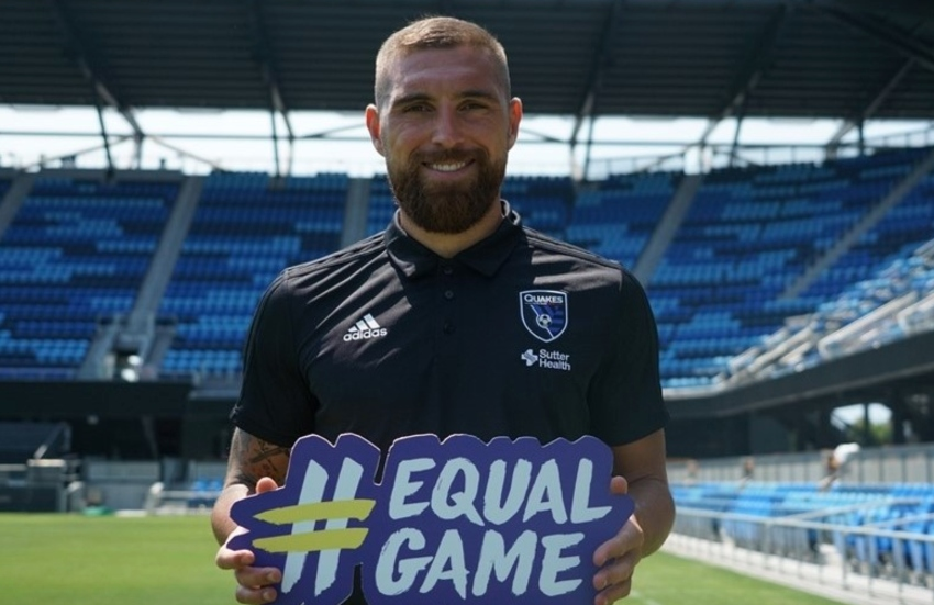 a man stands in an empty stadium holding a #equalgame sign and he is smiling