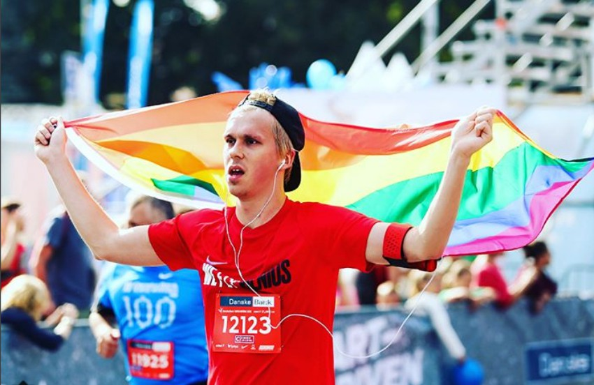 A runner in a red t-shirt and black backwards baseball cap runs with a rainbow flag over his head