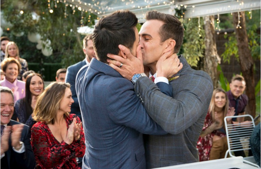 two men in suits kissing as people behind them clap and smile