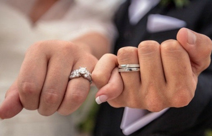 two hands one male and female intertwined at the pinky with engagement and wedding rings on
