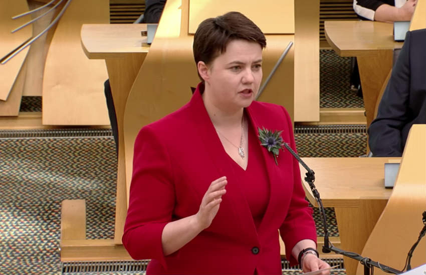 Scottish conservative leader Ruth Davidson while giving a speech in a red suit.