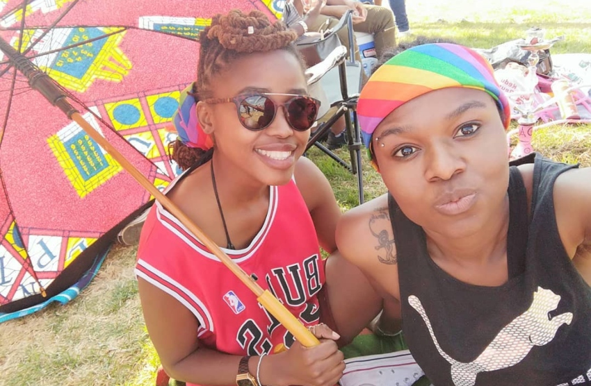 two women in a selfie one is wearing a rainbow bandana while the other is holding a red umbrella