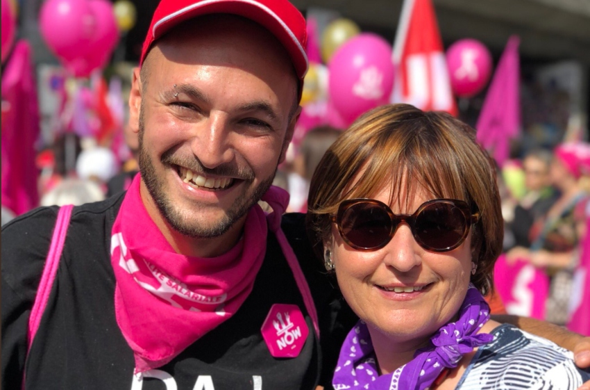 Mathias Reynard with an italian politician. he is wearing a pink cap and pink bandana they are outside at a rally