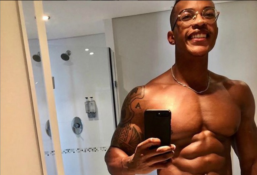 a selfie of a topless tumi seeco he is looking in the mirror and has an impressive six pack