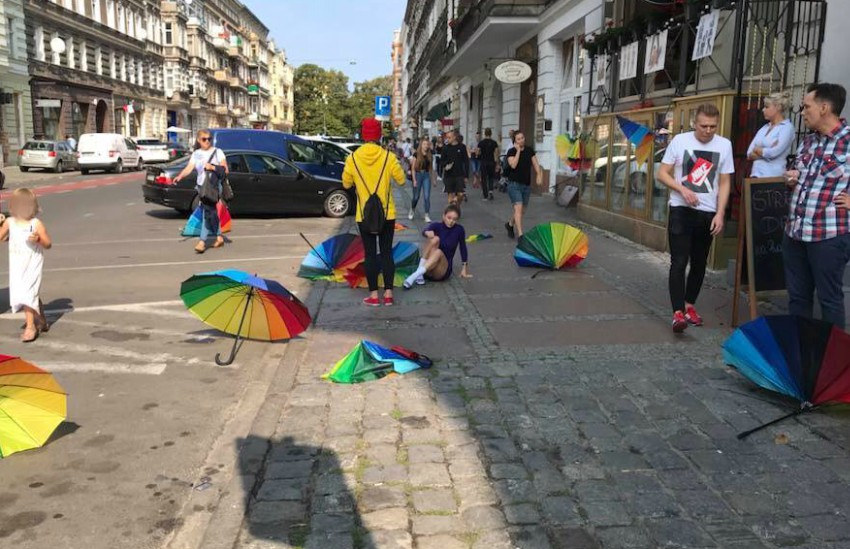 a girl fallen on the street surrounded by broken rainbow flags, people stand around her, some rushing to help her