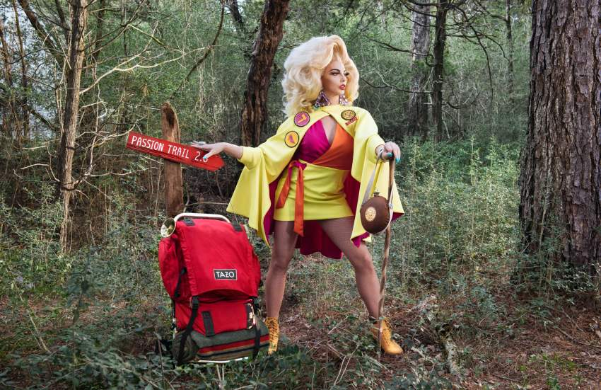 alyssa edwards in a red and yellow outfit standing outside surrounded by tress