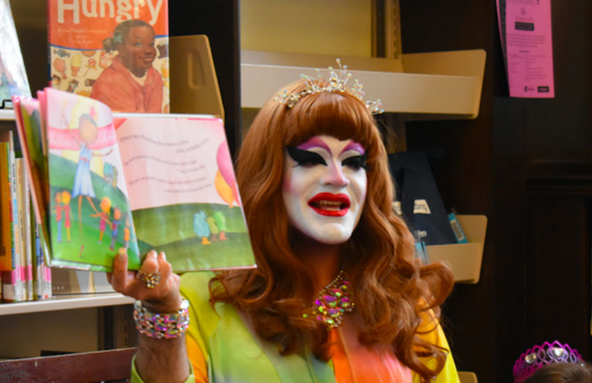 Drag queen reading a book to a library
