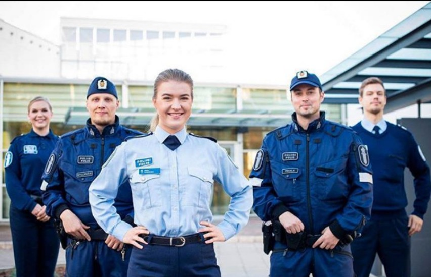 shot of arms in finland police jumpers on a desk with the hands touching the white paper