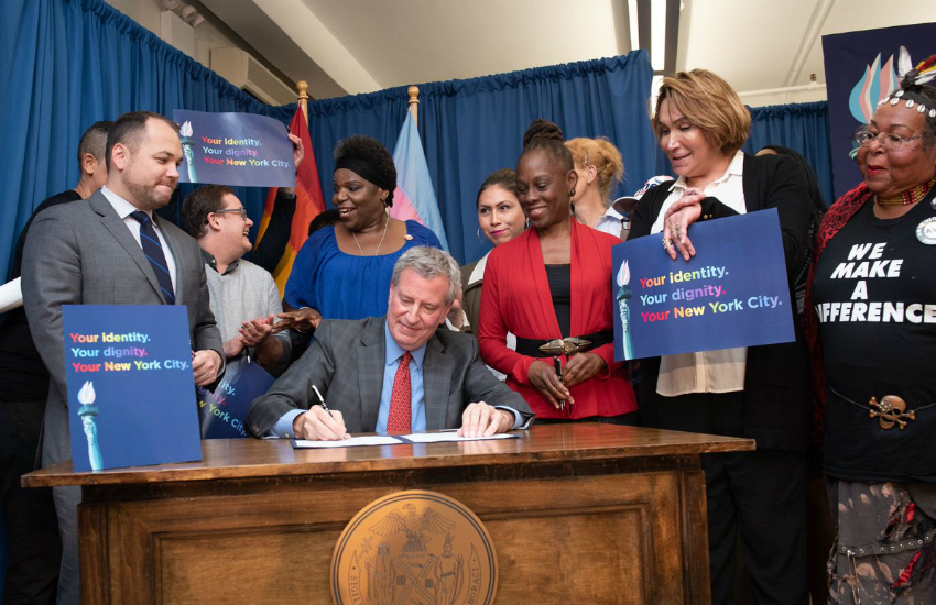 New York City Mayor Bill de Blasio signs the bill into law surrounded by members of the LGBTI community (Photo: Twitter)