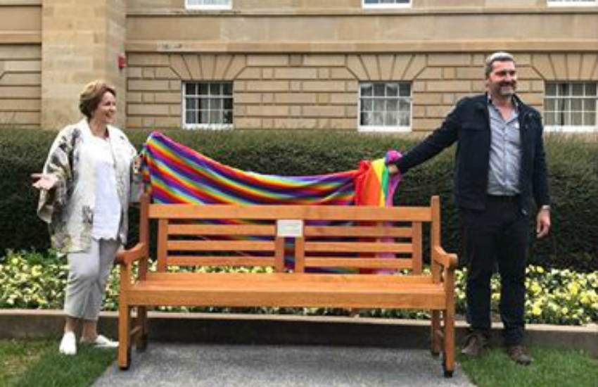 two people pulling a rainbow blanket off a parkbench