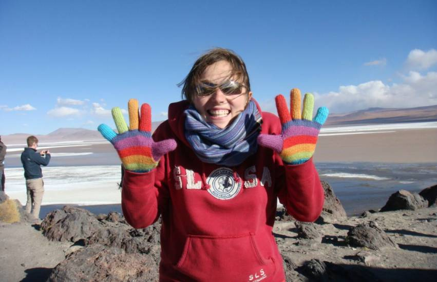 a woman standing outside somewhere cold, she is smiling and is holding up her hands which are covered by rainbow coloured gloves