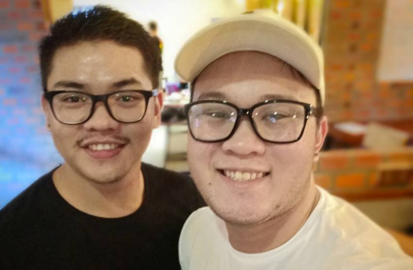 two men standing close to each other smiling up for a selfie