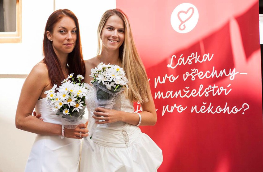 two women in bridal dresses holding flowers in front of poster with czech writing, they are both smiling