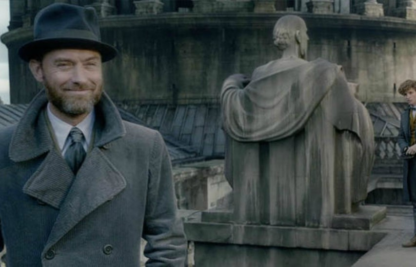 a smiling jude law in a trench coat and bowler hat