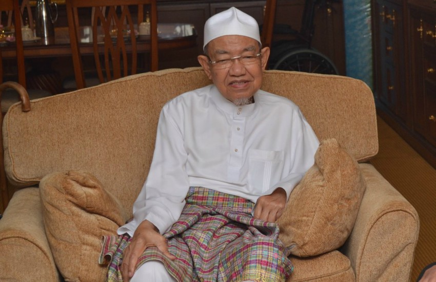 a man in traditional muslim malaysian costume sits in an armchair