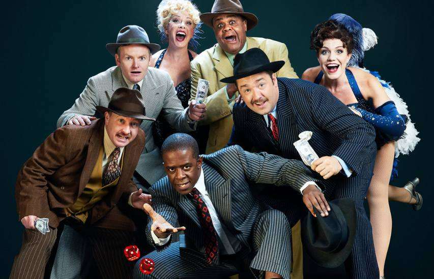 a press shot for guys and dolls with a group of men in suits and two burlesque dancers looking at dice being thrown in front of them