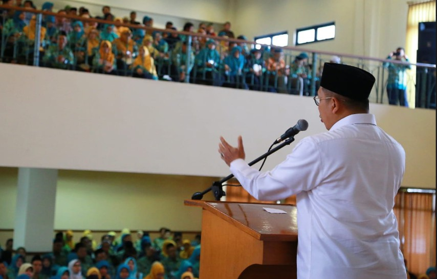 a photo behind Religious Affairs Minister Lukman Hakim Saifuddin who is standing at a podium on a stage talking to a crowd of school children in an audiotorium