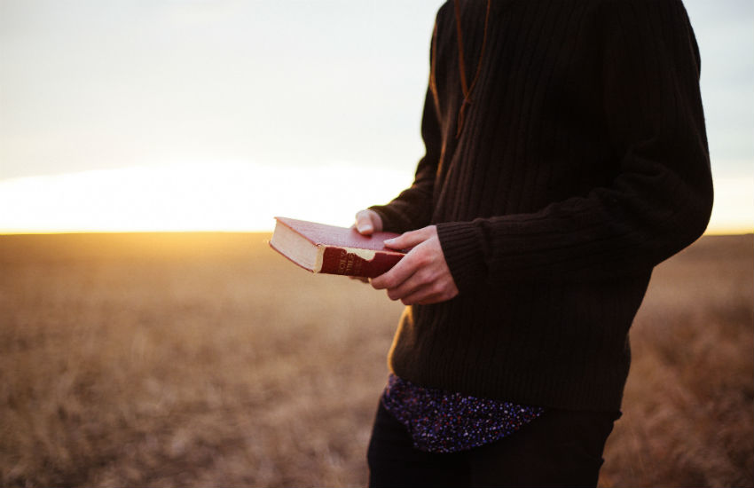 A young man holds a Bible