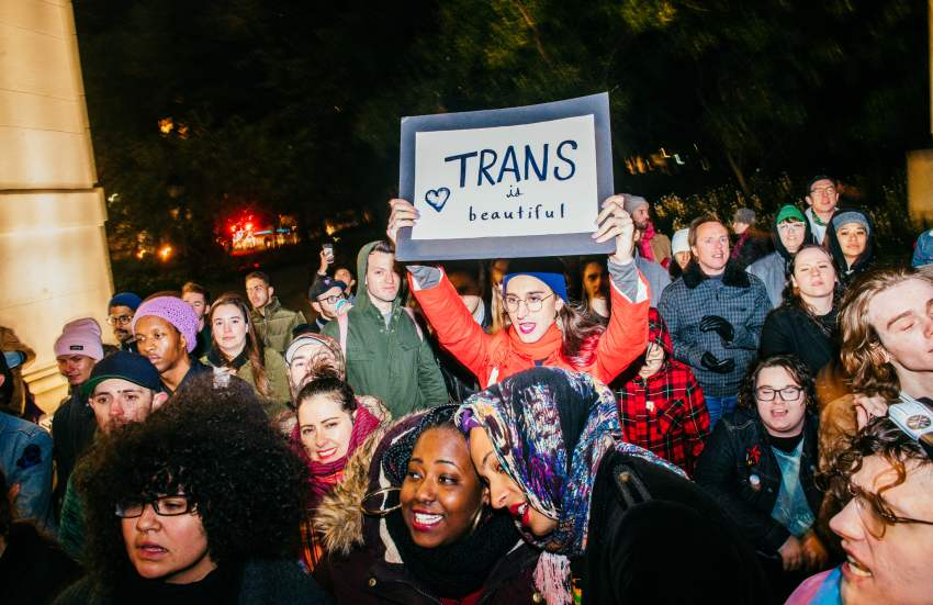 a person holds up a sign at a protest in favor of trans rights