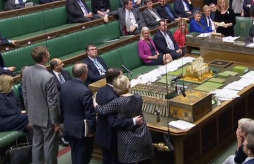 MPs in Northern Ireland's parliament hug after a historic vote