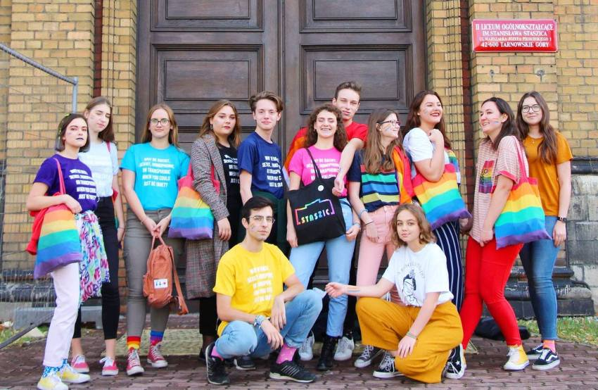 a group of teenagers stand outside in different rainbow colours