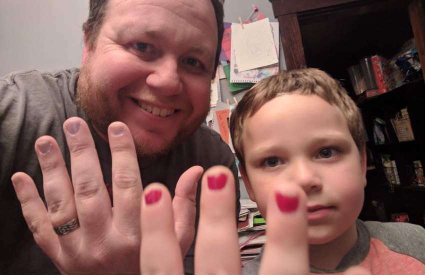 A dad and his son showing their painted nails on camera.