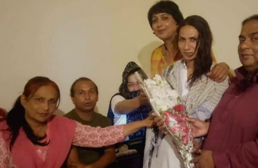 a group of people surrounded a woman holding a bouquet of flowers