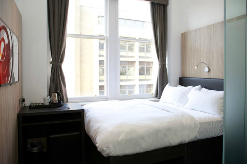 A bed with white sheets under big open windows