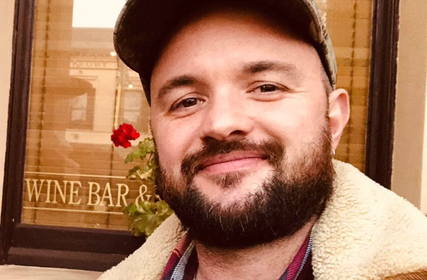 selfie of a guy with a beard wearing a baseball cap, smiling, with a beard sitting out the front of a restaurant