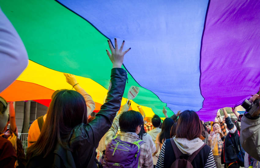 Marchers waving a giant rainbow flag above their heads in Hong Kong