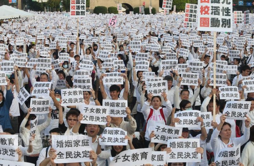 Anti-LGBTI rally in Taiwan, thousands of people holding white signs in Mandarin standing outside in a public square