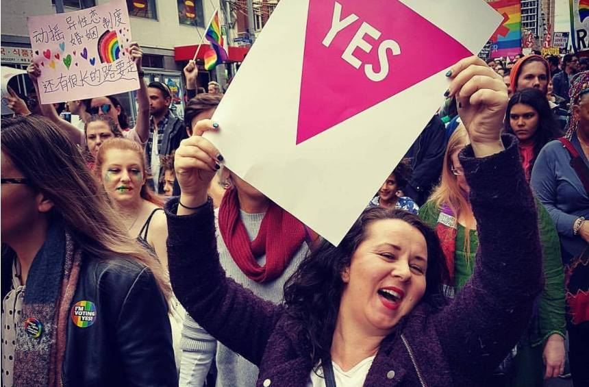 Shannon holding a yes sign up and smiling surrounded by thousands of people at a rally