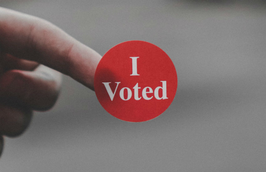 An 'I voted' sticker on a fingertip