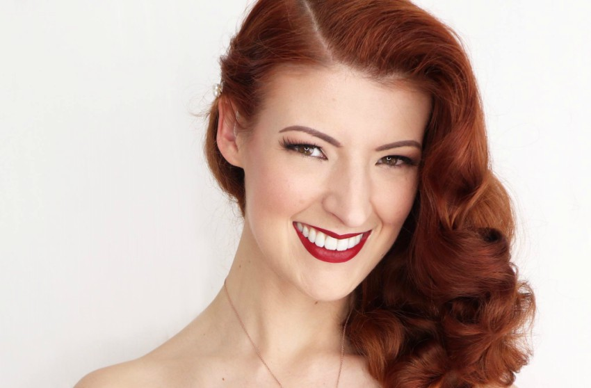 a woman with red hair smiling at the camera