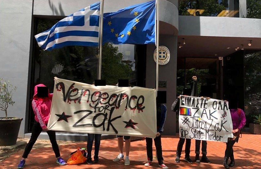 protesters standing outside holding banners with the greek and european flag on a flag pole behind them