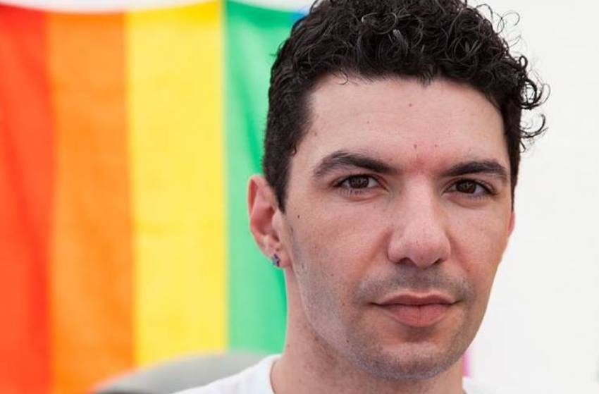 close up of a man's face with short dark hair and a rainbow pride flag hangs behind him