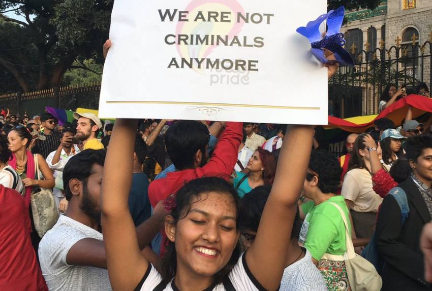 a girl stands in a crowd with a sign over her head saying 'we are not criminals anymore'