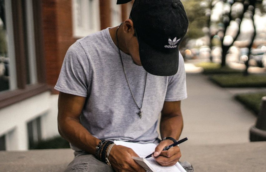 A young black person writing in a notebook