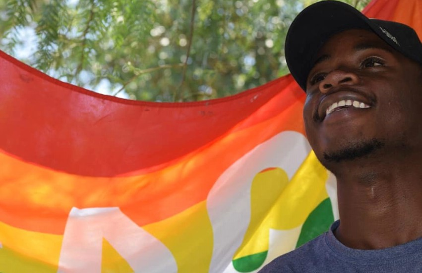man standing in front of rainbow flag, smiling