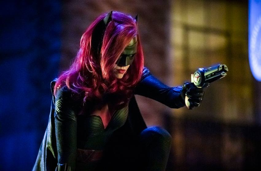 ruby rose as batwoman with red hair and a black mask she is crouching, pointing a gun